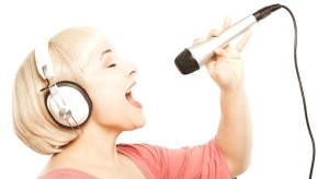 Young blonde with headsets and microphone against white background